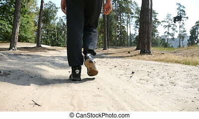 Man`s feet in sneakers walk along some forest path on a sunny day in slow motion