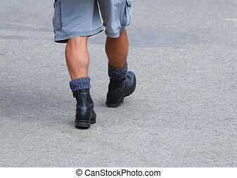 Man's hairy feet in army boots