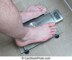Man's feet on weight scale - Alert