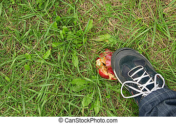 Man's foot crushing a red apple