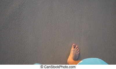 Point of view looking down at male legs in blue shorts and bare feet walking on the sandy beach