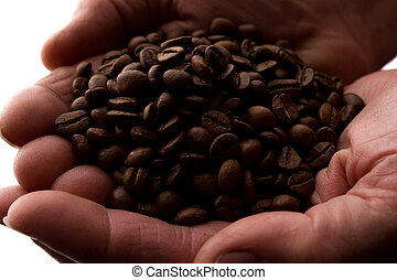 Man's hand a handful of coffee beans - silhouette