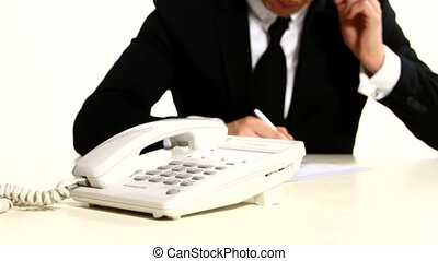 man's hand dials phone number. In the background planet businessman