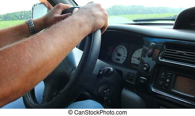 man's hand driving in car close-up