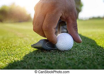 man's hand exposes a Golf ball