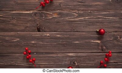 Man's hand fills wooden christmas background with fir branches, elderberries and christmas balls. Merry Christmas