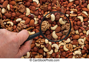 Man's hand holding a magnifying glass over the nuts