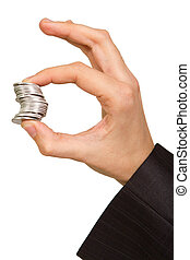 man's hand holding a stack of silver coins
