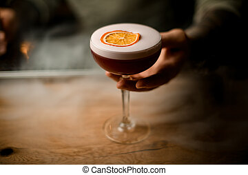 man's hand holding glass of drink with foam at smoky bar counter.