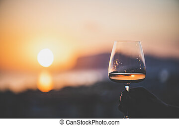 Man's hand holding glass of wine with sea at background