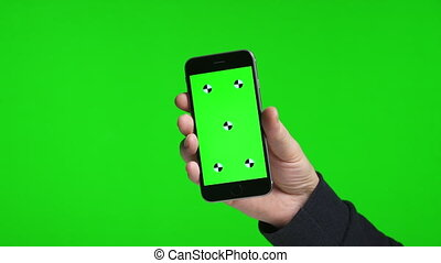 Man's hand holding showing a green screen of a phone, over...