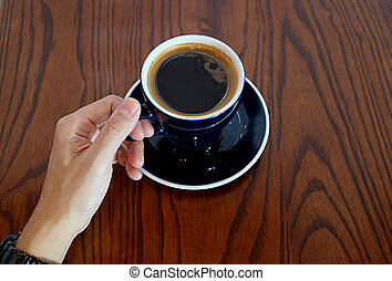 Man's Hand Holding the Cup of Hot Coffee Served on Wooden Table