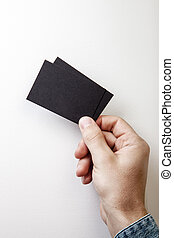 Man's hand holding two black business cards