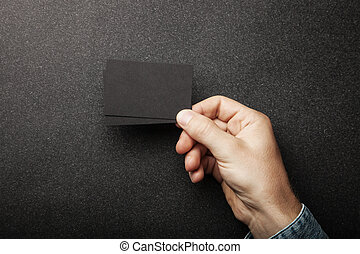 Man's hand holding two business cards on the black texture