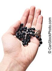 hand holding wooden rosary with Catholic crucifix