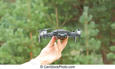 Man's hand holds a drone or a quadrocopter and lets fly out...