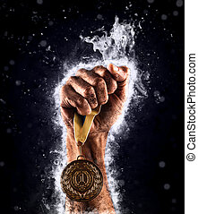 Man's hand in a blue fire is holding up gold medal. Winner...