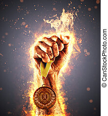 Man's hand in a fire is holding up gold medal. Winner in a...