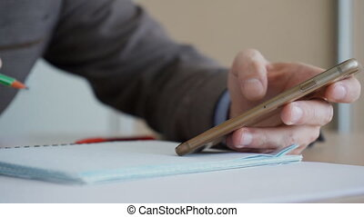 Man's hand in suit holds phone in hand and writes with pen.