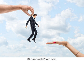 Man's hand is carrying a little businessman to a woman's hand on the backgroung of blue sky