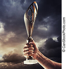 Man's hand is holding gold cup against of the gloomy stormy sky.