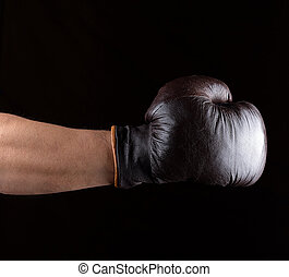 man's hand is wearing a brown leather boxing glove