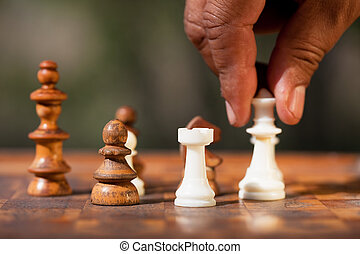 Man's hand making a move on the chessboard