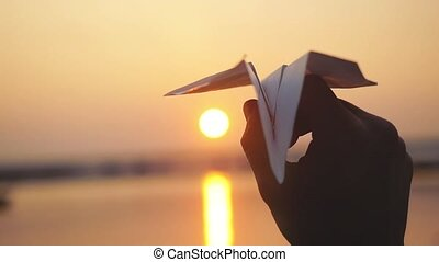 Man's hand of launch paper plane against the sea during...