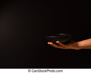 Man's hand on a black background with a plate of food