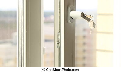 Man's hand on secure window handle