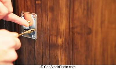 man's hand opens a lock with a key in the door.