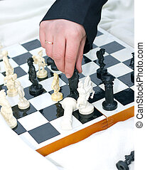 man's hand over the chess board