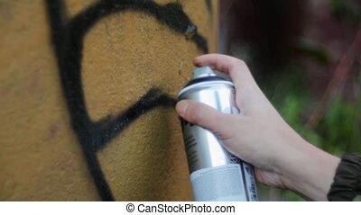 Man's hand paint spraying graffiti on the wall. Summer day.  Close up. Vandalism