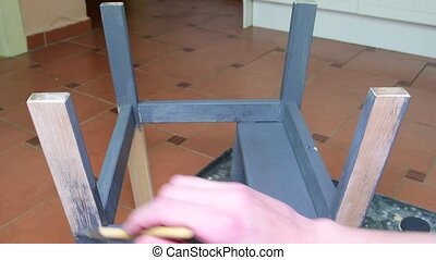 Man's hand paints the furniture step stool . Gray coating....