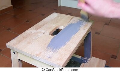 Man's hand paints the furniture step stool . Gray coating. Painting step stool with grey color