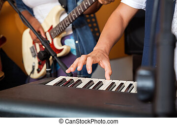 Man's Hand Playing Piano In Recording Studio - Closeup of...