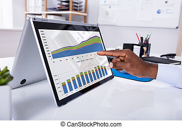 Man's Hand Pointing On Graph At Laptop