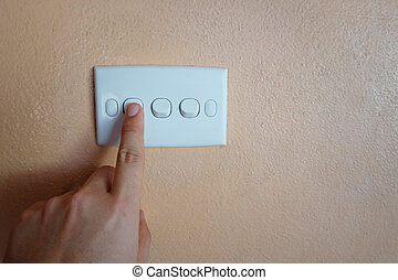 Man's hand push button of white switch on orange wall.