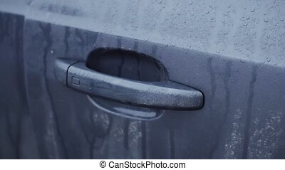 Man's hand push wet handle of door and open car. Close up....