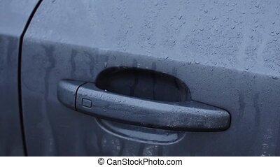 Man's hand push wet handle of door, open car. Close up....