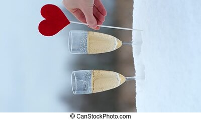 Valentines day celebrating. Vertical video of mans hand put red heart on stick into snow near glasses with champagne.