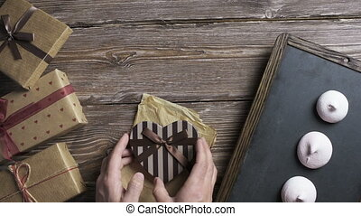 Mans hand puts heart shaped gift box to wooden desktop - Top...