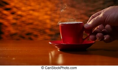 Man's hand putting a cup of hot coffee on the table. Slow motion