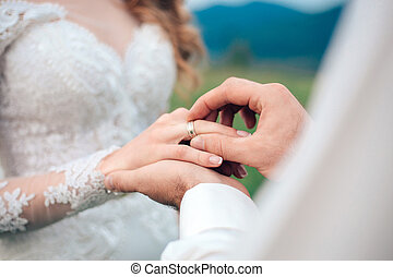 mans hand putting a wedding ring on the brides