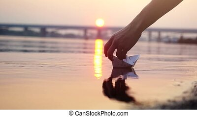 Man's hand putting paper boat on the water and pushing it away during beautiful sunset with reflection sun in the sea on blurred bridge background. 3840x2160