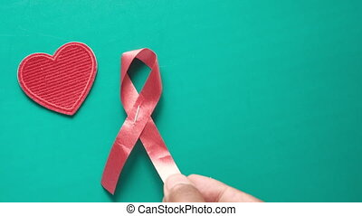 man's hand putting Red ribbon HIV on green background .
