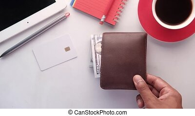 man's hand putting wallet on table .