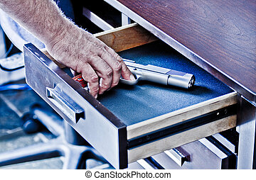 Mans hand reaching for handgun in desk drawer