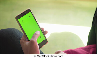 Man's hand scrolling smartphone with green screen
