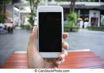 Man's hand shows mobile smartphone in vertical position,...